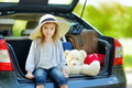 Little girl going to a car vacation adorable in summer hat leaving for with their parents Stock Photos