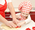 Little girl and grandmother cut dough with form for cookies in kitchen Royalty Free Stock Photo