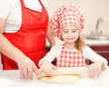Little girl and grandmother rolling dough for cookies in kitchen Stock Images