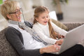Little girl and granny together using laptop at home happy Royalty Free Stock Photo