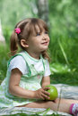 Little girl with green apple in her hands Royalty Free Stock Image
