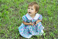 Little girl on green glade sitting and eating berries Royalty Free Stock Photo