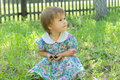 Little girl on green glade sitting and smiling with berries Royalty Free Stock Photo