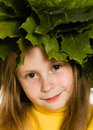 Little girl with green maple leaves on the head Stock Image