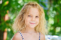 Little girl in green summer city park portrait of beautiful smiling Stock Photos