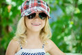 Little girl in green summer city park portrait of beautiful smiling with sunglasses Royalty Free Stock Images