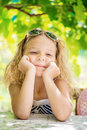 Little girl in green summer city park portrait of beautiful smiling with sunglasses Royalty Free Stock Image