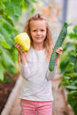 Little girl in greenhouse with green pepper and cucumber in hands. Time to harvest. Big basket full of vegetables Royalty Free Stock Photo