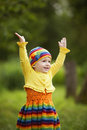 Little girl greets hands up funny outdoors Stock Photos