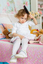 Little girl with hairbrush combing hair sits on the bed in children room year old Stock Photos