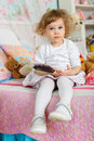 Little girl with hairbrush combing hair sits on the bed in children room year old Royalty Free Stock Photography