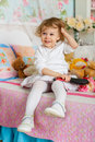 Little girl with hairbrush combing hair sits on the bed in children room year old Royalty Free Stock Photos