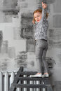 A little girl with hand raised standing on ladder at gray wall Stock Photo