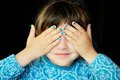 Little girl with hands covering her eyes Stock Image