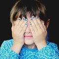 Little girl with hands covering her eyes Royalty Free Stock Photo