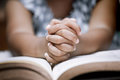 Little girl hands folded in prayer on a Holy Bible Royalty Free Stock Photo