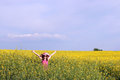 Little girl with hands up on yellow flower field Royalty Free Stock Photo