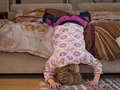 Little girl hanging off the side of a bed balancing her head and hands on floor as she amuses herself playing Royalty Free Stock Image