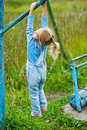 Little girl hanging on old exercise beautiful equipment in deserted park Stock Images