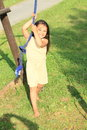 Little girl hanging on rope barefoot in yellow dress blue Royalty Free Stock Images
