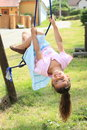 Little girl hanging on rope in blue skirt and pink t shirt blue Stock Images