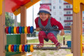 Little girl in hat climbs on children playground at sunny Royalty Free Stock Photo