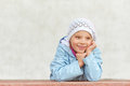 Little girl in hat and jacket beautiful blue around school building Stock Photography