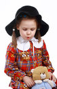 A little girl in the hat plays with a teddy bear Royalty Free Stock Photography