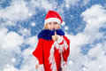 Little girl in hat of Santa Claus on background of sky Royalty Free Stock Photo