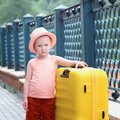A little girl in a hat is standing next to a large suitcase. A beautiful portrait of a child. Royalty Free Stock Photo