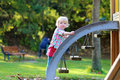 Little girl having fun at playground happy child blonde curly toddler in bright casual outfit climbing brave on the on a sunny day Stock Photos