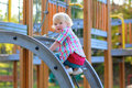 Little girl having fun at playground happy child blonde curly toddler in bright casual outfit climbing brave on the on a sunny day Royalty Free Stock Image