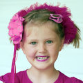 Little girl headshot portrait of with green eyes and purple hair accessories Royalty Free Stock Photos