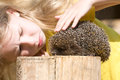 Little girl and a hedgehog looking at funny side view Stock Photo