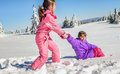 Little girl helping her friend to get up on the snow Royalty Free Stock Photo
