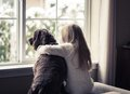 Little girl and her dog looking out the window on a snowy day Stock Photos