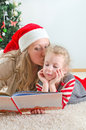 Little girl and her mom reading book at christmas Royalty Free Stock Photos