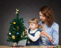 Little girl and her mummy decorates the christmas tree dark background Stock Image