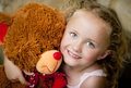 Little girl her teddy sitting front old door Stock Image