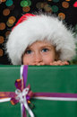 Little girl hiding behind a christmas gift Stock Photos