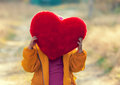 Little girl hiding behind heart shaped pillow Royalty Free Stock Photo