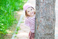 Little girl hiding behind a tree Royalty Free Stock Photography