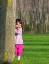 Little girl hiding behind a tree in a forest in spring Royalty Free Stock Photo