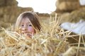 Little girl hiding in the hay close up portrait of a at a farm Stock Image