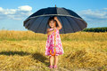 Little girl hiding under big umbrella happy black in fair weather Royalty Free Stock Photography
