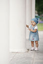 Little girl hiding in white columns Royalty Free Stock Image
