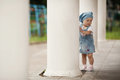Little girl hiding in white columns Stock Image