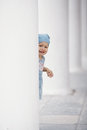 Little girl hiding in white columns Stock Images
