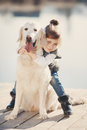Little girl with his beloved dog at the lake Royalty Free Stock Photo