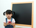 Little girl holding apple portrait of in front of the blackboard Stock Photos